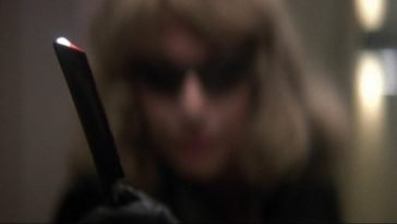 Man disguised as a woman in a blonde wig and black sunglasses holds out a razor menacingly.