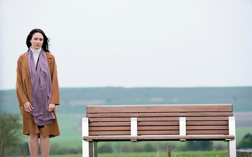 Lisa stands outside by a bench near a field