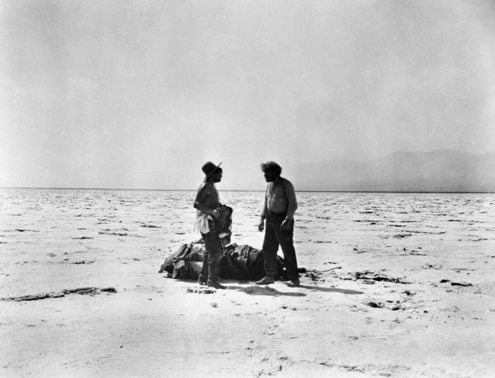 Two figures in the harsh desert landscape of Death Valley