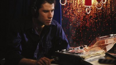 Jack (John Travolta) listening to a recording through headphones.