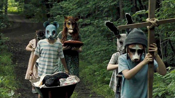 children with animal masks stare at camera