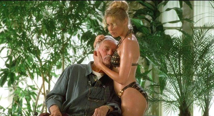 An older man rests his head against the chest of a bikini clad young blonde woman