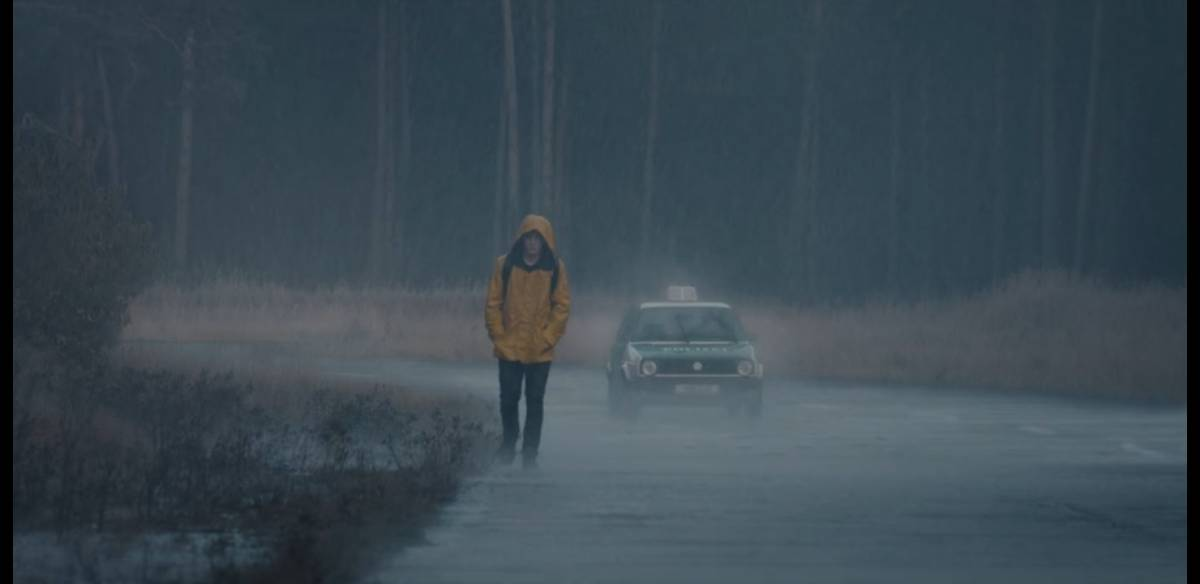 Jonas Kahnwald walking along the road in the rain next to a police car in Netflix's Dark
