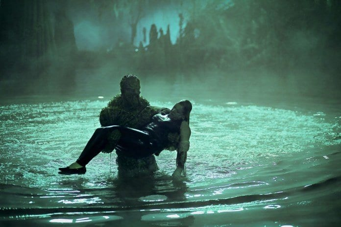 Swamp Thing (Derek Mears) carriies Maria (Virginia Madsen) to safety out of the swamp.