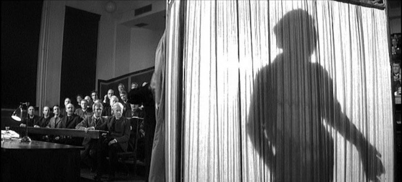 An audience looks on as the silhouette of John Merrick shows him standing behind a curtain