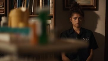 Rue (Zendaya) looks stricken at pill bottles that are blurred in foreground of image.