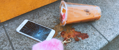 An iphone with a smashed screen, a pink fluffy keyring and a spilled orange and red drink on a step