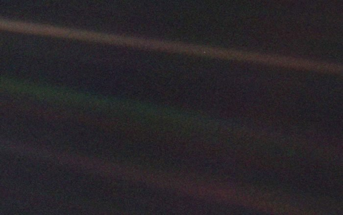photo taken by Voyager 1 of Earth, seen as a pale blue dot in the top beam of light