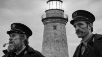 two men stare out into the sea with a lighthouse in the background