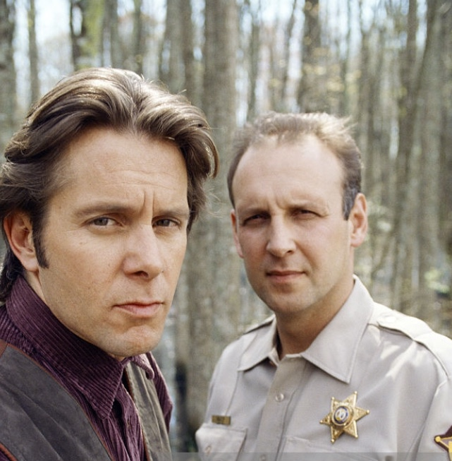 Sheriff Buck and Deputy Healy look to camera in a wooded area
