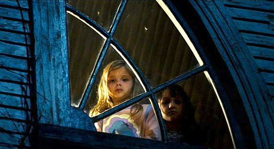 Little girl Chelsea looks out the upstairs window of her house, the ghost child Jodie standing next to her in The Amityville Horror (2005).