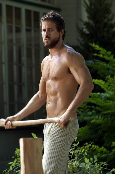Shirtless man George Lutz menacingly holds an axe while chopping firewood in The Amityville Horror (2005).