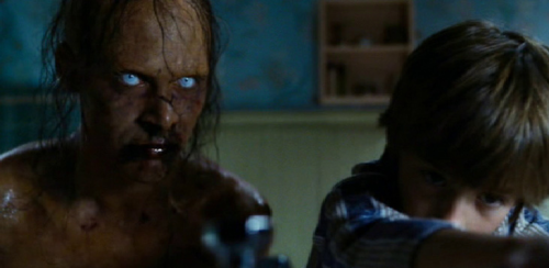 A decaying, yellow-skinned ghosts with blood coming out it's mouth appears next to boy Michael Lutz in the bathroom in The Amityville Horror (2005).