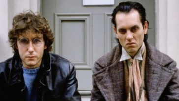 Withnail and Marwood sitting on a doorstep looking into the camera