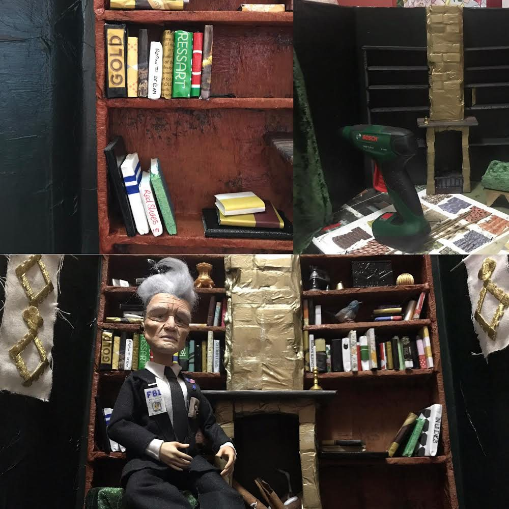 Doll of David Lynch sitting in a room of books