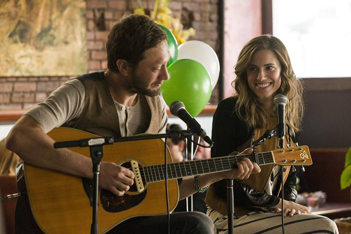 Desi (Ebon Moss-Bachrach) and Marnie (Allison Williams) perform an acoustic set in a cafe in Girls