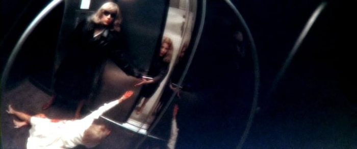 Woman outside an elevator reaches inside to a bloody woman pleading for help, while a man disguised as a woman drops a razor into the hand of the woman outside the elevator.