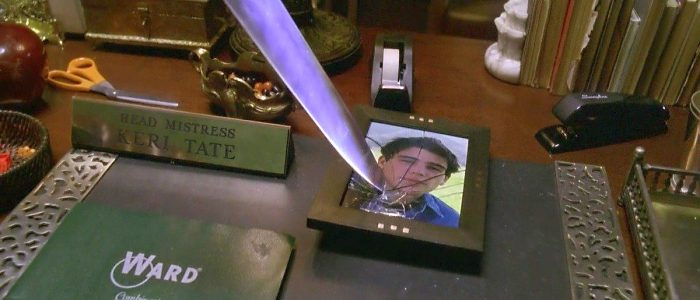 A knife shatters a photo of John Tate on the desk of Laurie Strode