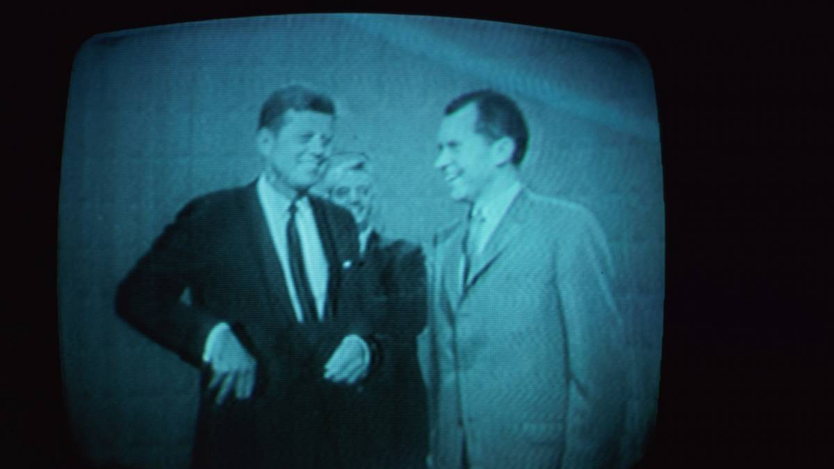 JFK and Nixon stand next to each other on TV prior to their debate