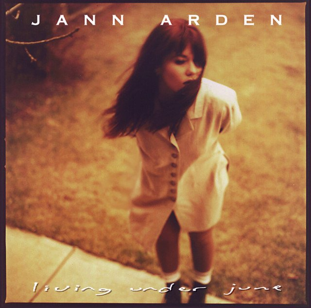 the cover to Jann Arden's Living Under June is a sepiatone shot from above of the singer, hair in her face and arms behind her back looking pensive.