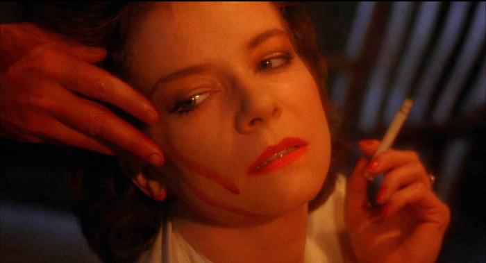A hand wipes blood on Julia's face in Hellraiser