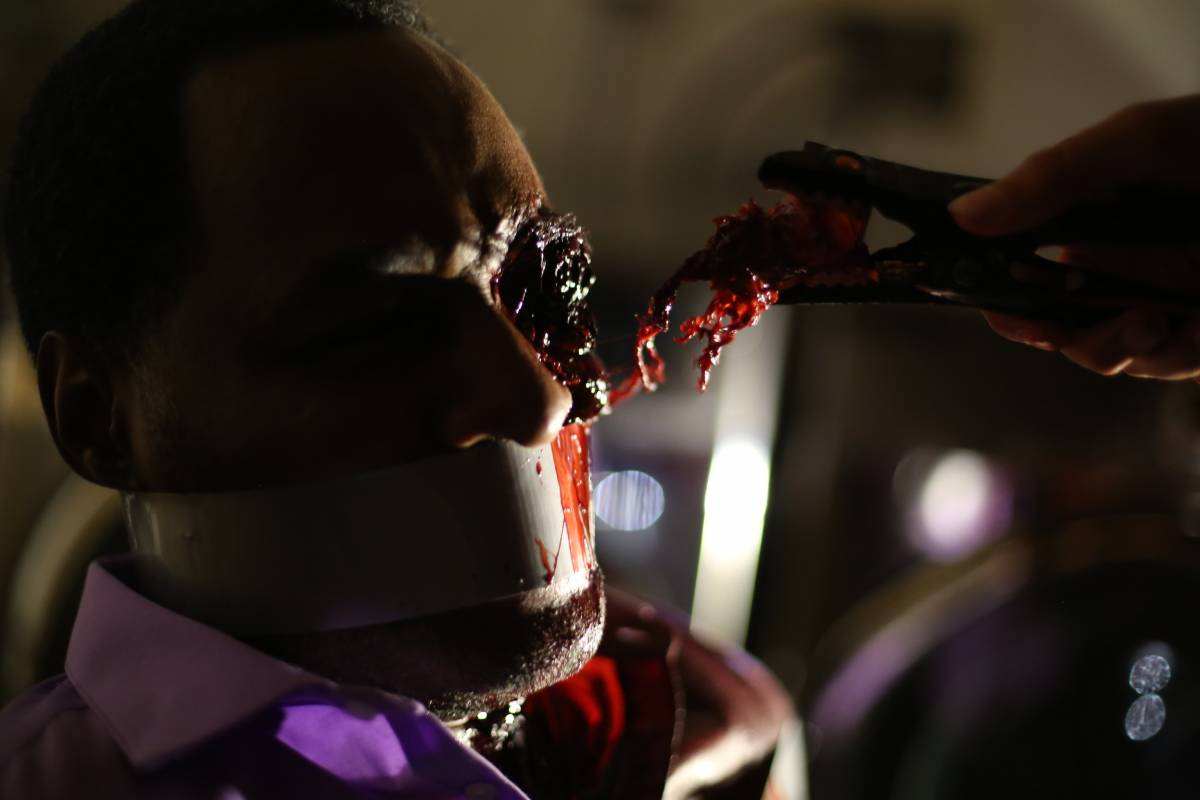 A man tied to a chair and gagged has his eyeball removed by pliers