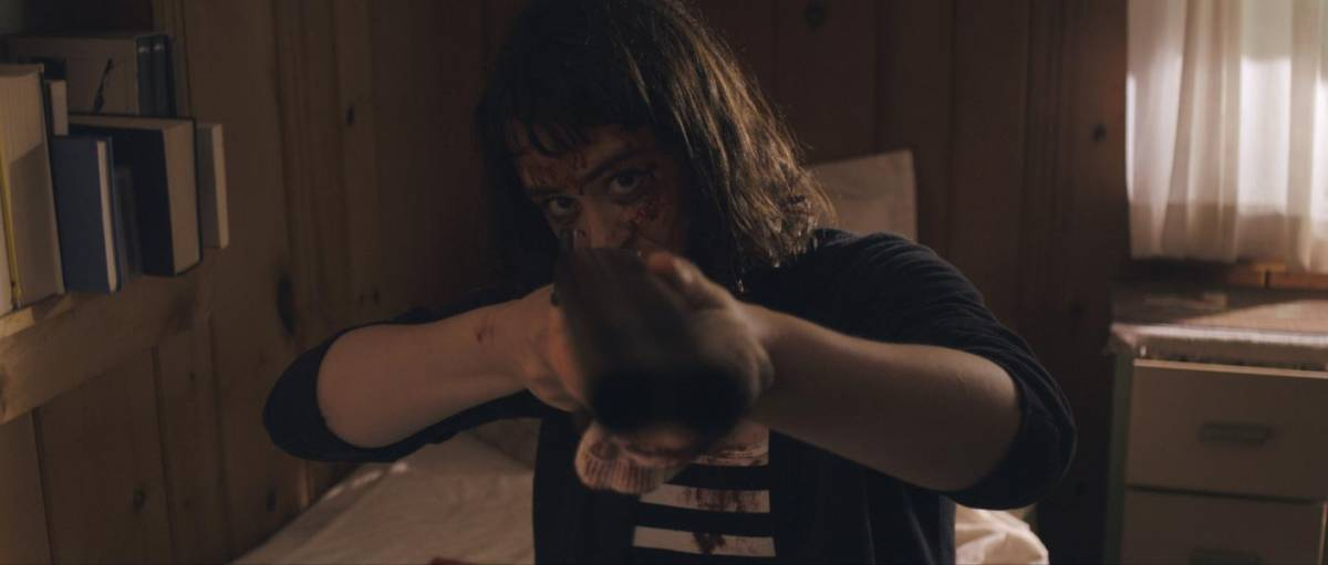 Hoffman as Amanda pointing a shotgun at the camera in Get My Gun
