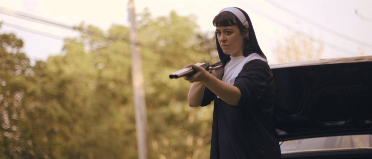 Hoffman as Amanda with a gun in Get My Gun