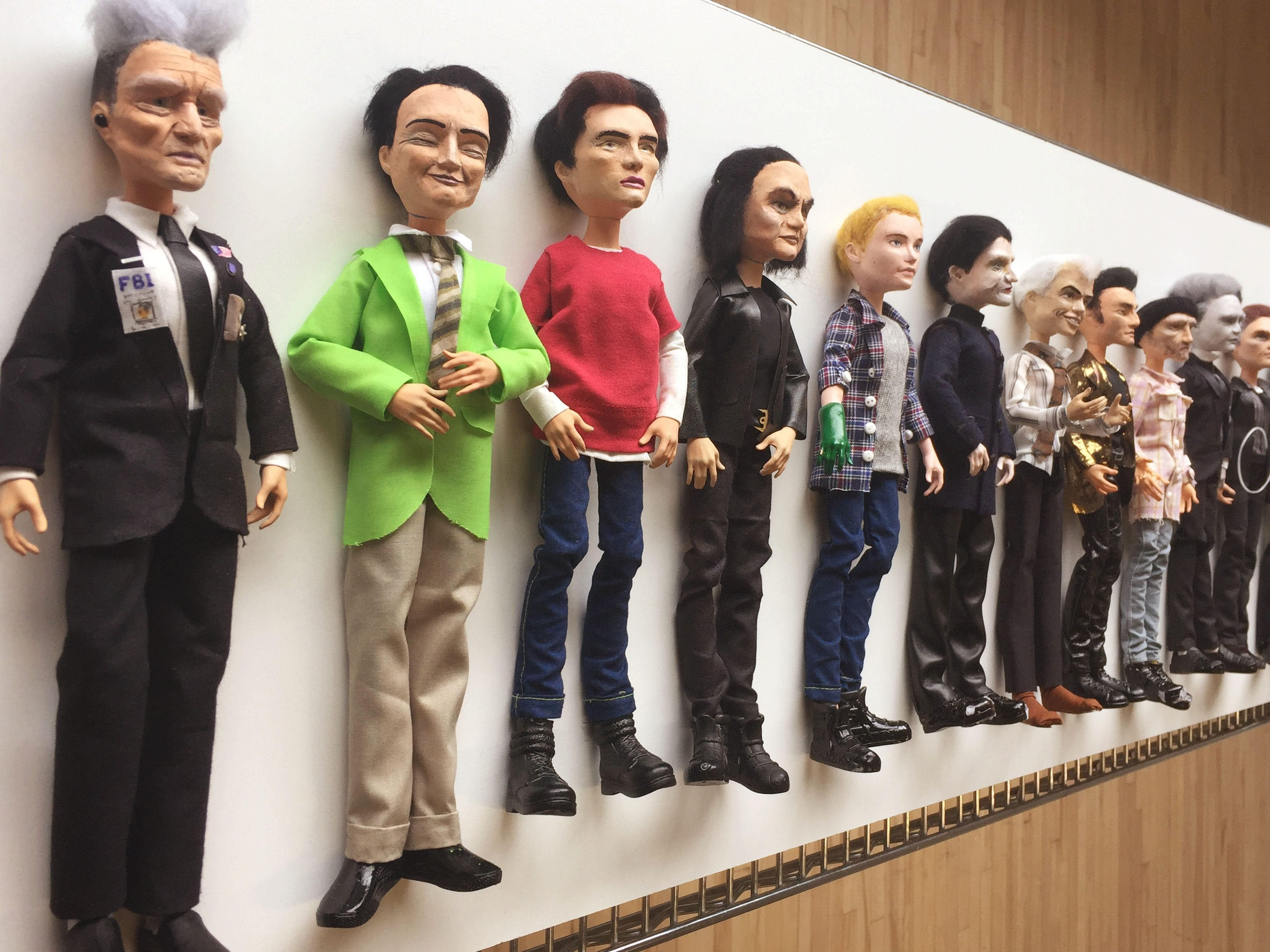 Men of Lynch dolls lined up against a wall
