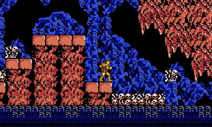 Simon waits for a moving platform to cross a dangerous waterway in the skull littered caverns.