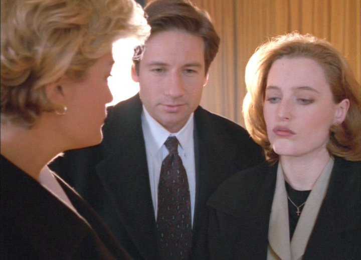 Detective White speaks to Agents Mulder and Scully, while Scully looks down disdainfully.