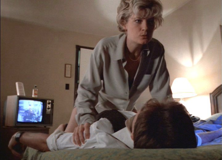Detective White aggressively straddles Agent Mulder on the bed in his hotel room.
