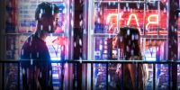 Tessa and Hardin talk in the rain with neon signs behind them