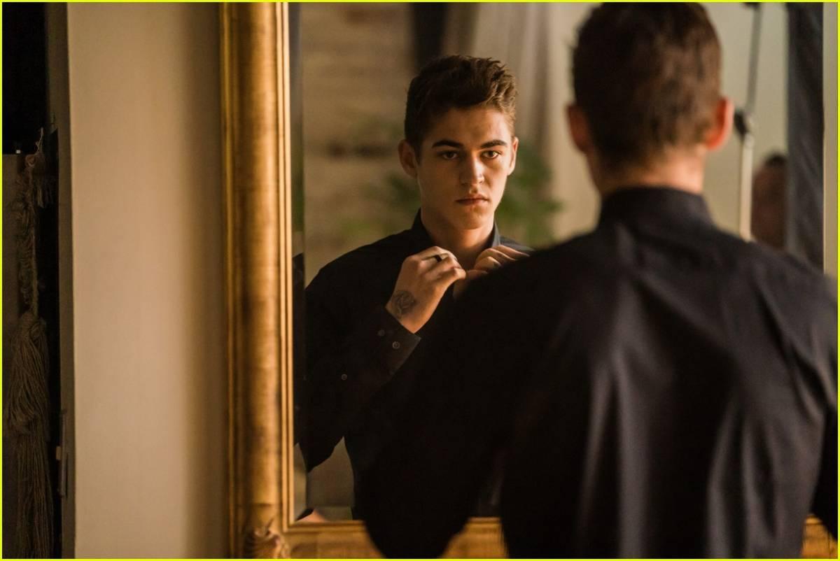 Hardin Scott, played by Hero Fiennes-Tiffin, straightens his collar in the mirror