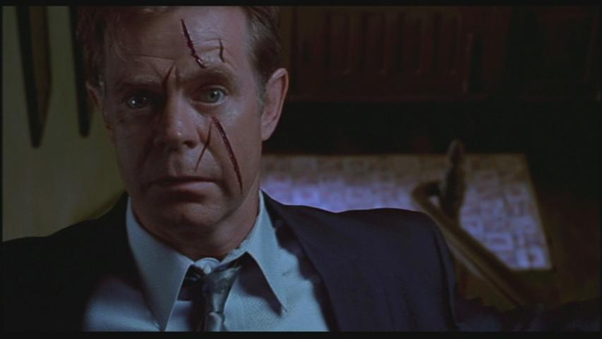 William H. Macy as Detective Arbogast stands at the top of a staircase with a slashed face