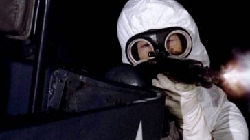 An army man wearing a white suit and gas mask points a gun at people