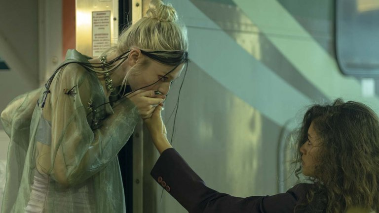Jules kisses Rue's hand while Jules stands on train and Rue stands on train platform.