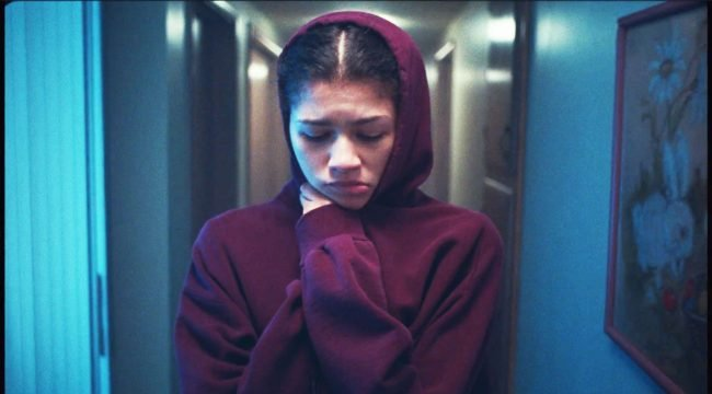 Rue looks down while pulling a red hoodie up around her chin.