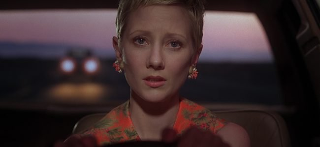 Close-up shot of Anne Heche as Marion crane driving down the highway with a sunset and headlights in the background.