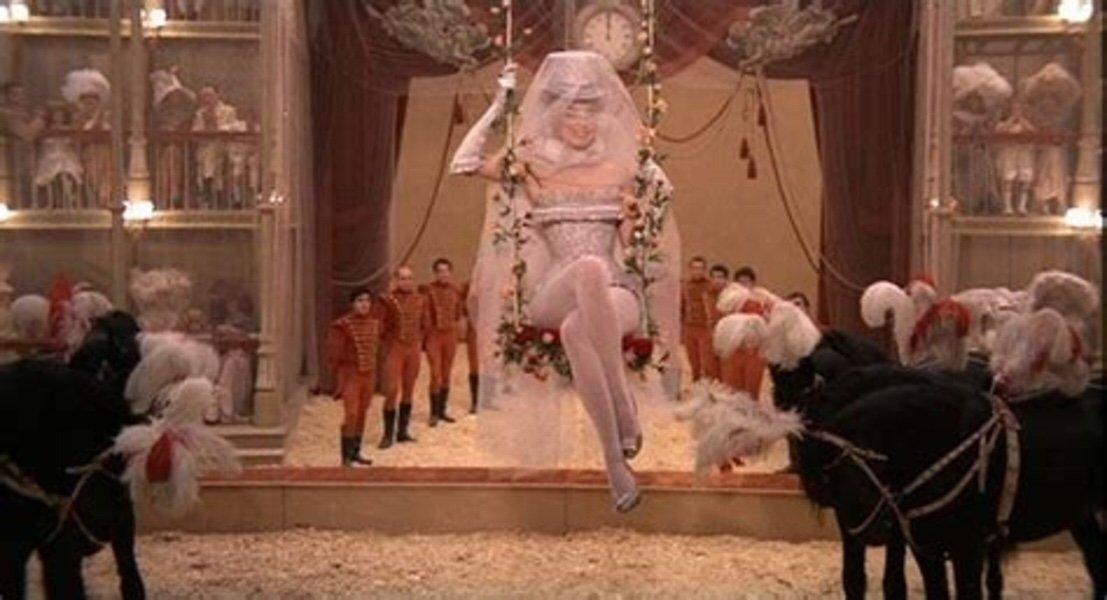 A ballerina rides a swing at the circus