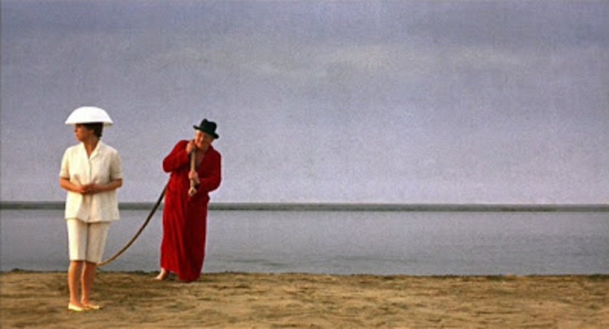 Giulietta (Giulietta Masina) on the beach with a man pulling a rope from the ocean.