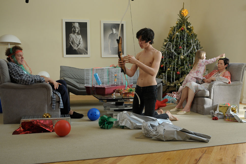 Kevin (Ezra MIler) unboxes his future weapon for Christmas while Eva (Tilda Swinton) looks on distraught