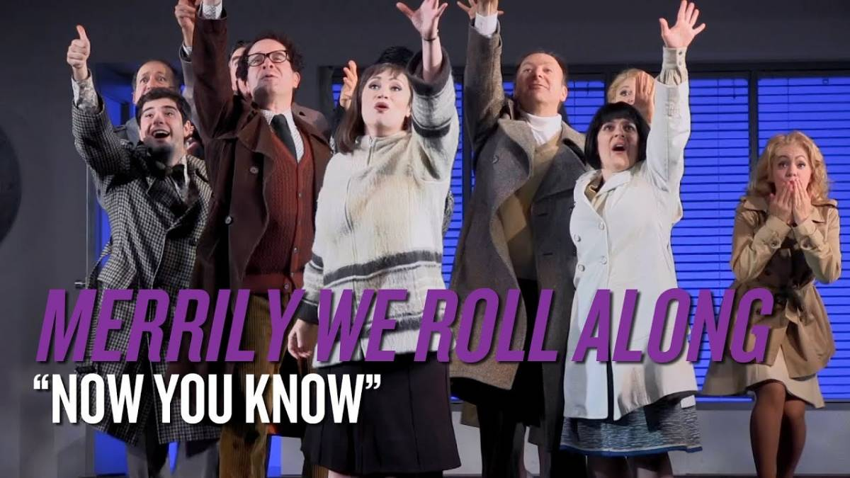 """A scene from a revival. The cast is onstage together, each with an arm raised up. The caption reads """"Now You Know"""", which is the song from this scene."""