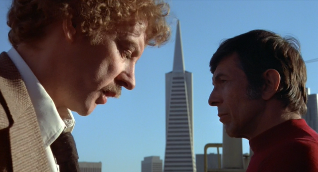 Leonard Nimoy and Donald Sutherland in Invasion of the Bodysnatchers, outside with a tall building in the distance between them