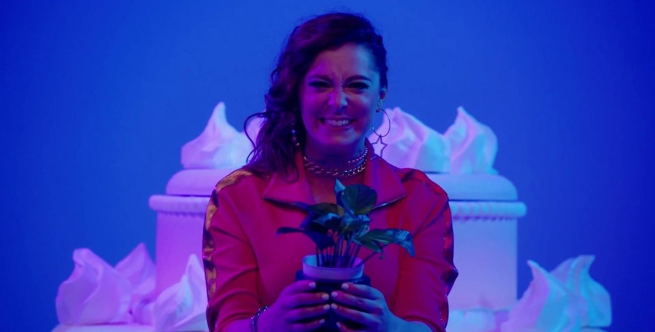 Rebecca (Rachel Bloom) holds a plant with a forced smile on her face