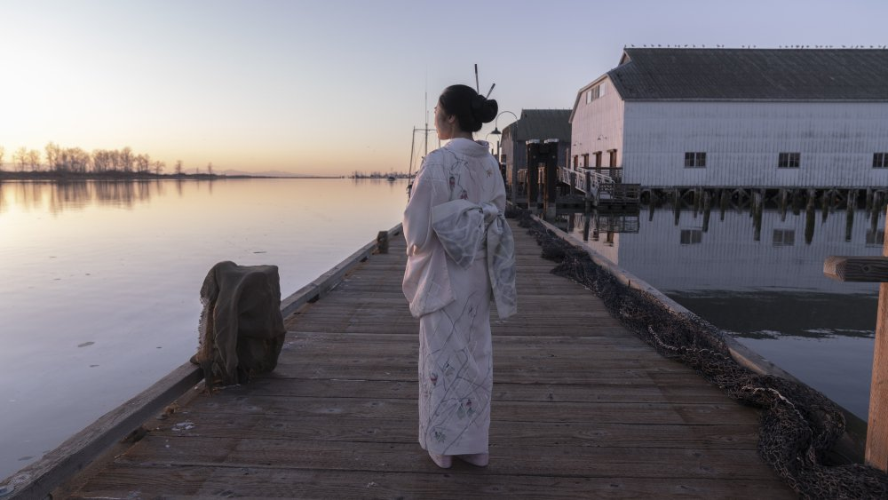 Mrs Furuya walks along the jetty looking at the sea in the twilight
