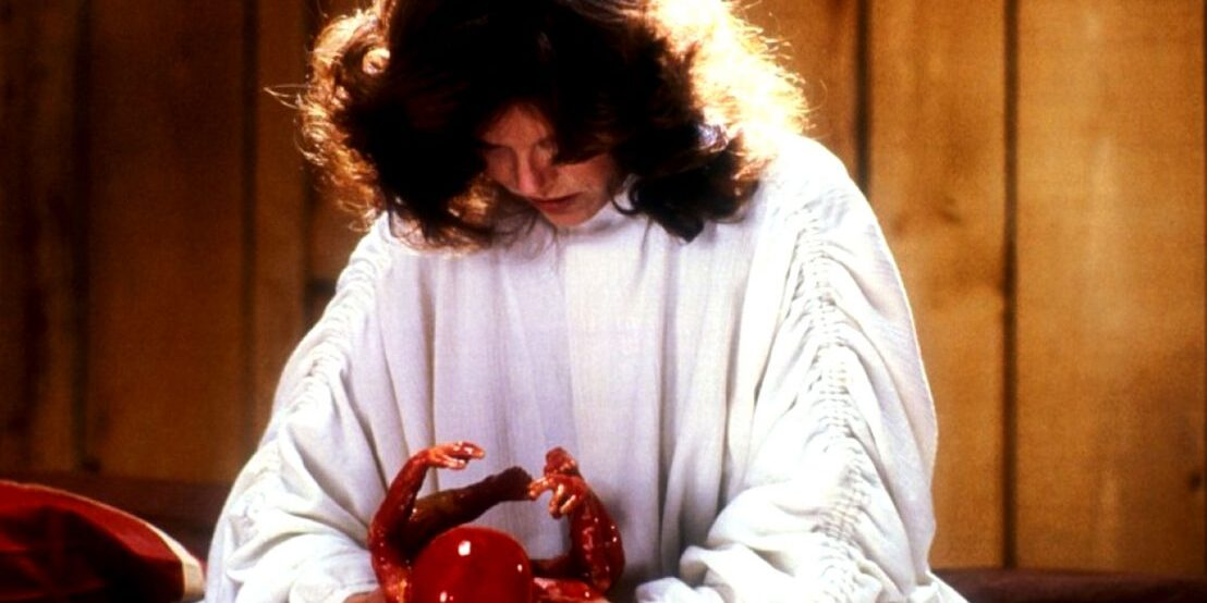 a woman holds a bloody newborn baby in The Brood