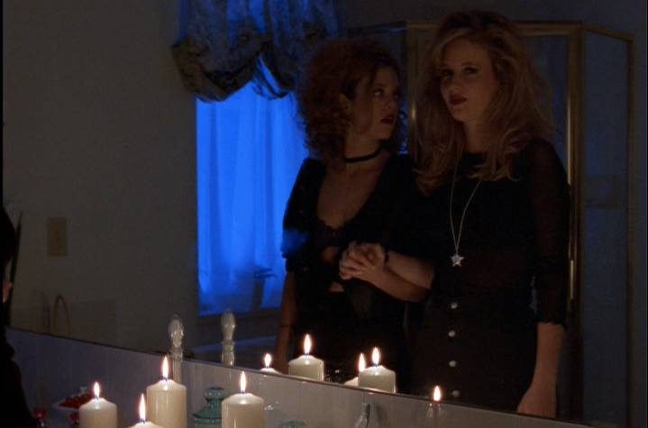 Terri and Margi stand in front of a bathroom mirror with lit candles playing Bloody Mary.