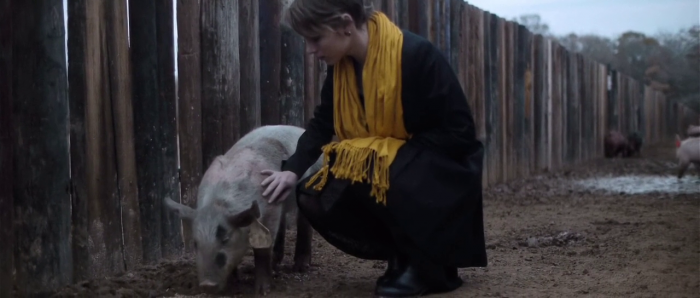 Kris (Amy Siemetz) kneels to stroke a pig in a muddy pen.