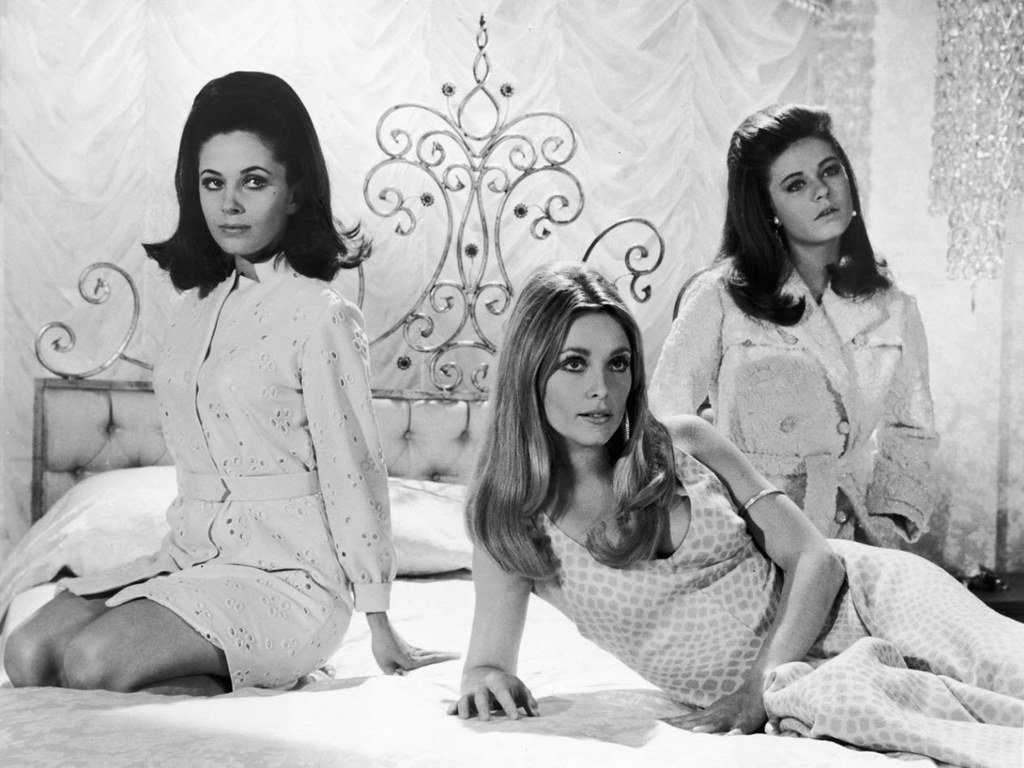 Sharon Tate with her co-stars Patty Duke and Barbara Parkins sat on a bed in Valley of the Dolls